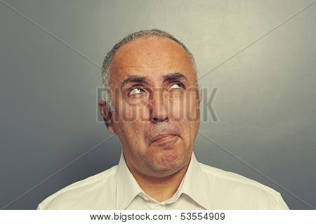 pensive senior man looking up over dark background