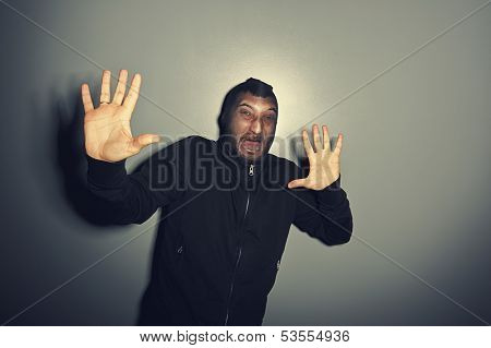 criminal man screaming and raising hands up over grey background