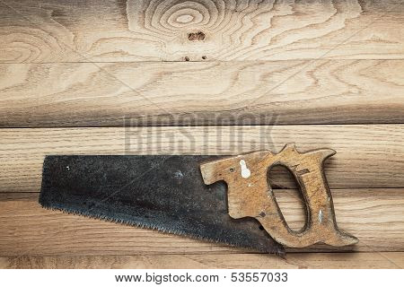 old rusty saw on table