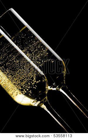 Detail Of A Pair Of Tilted Flutes Of Champagne With Golden Bubbles