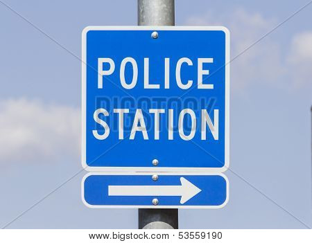 Police Station direction sign with blue sky.