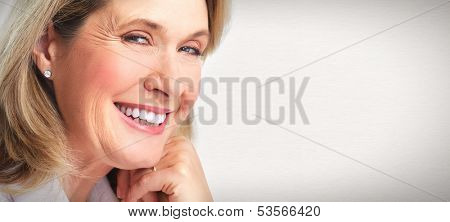 Senior smiling woman portrait. Over grey background.