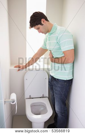 Side view of a young man with stomach sickness about to vomit into the toilet