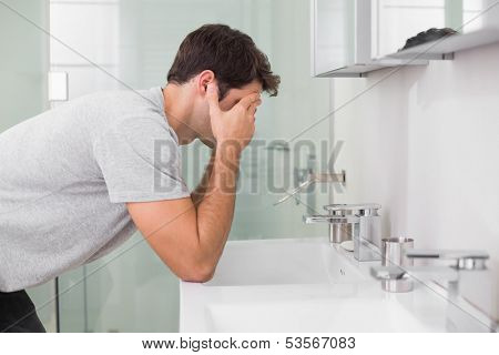 Side view of a young man with head in hands at washbasin in bathroom