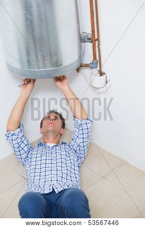Concentrated young technician servicing an hot water heater