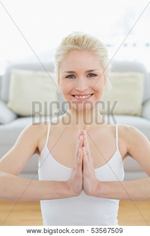 Portrait of a toned young woman sitting in Namaste position at fitness studio