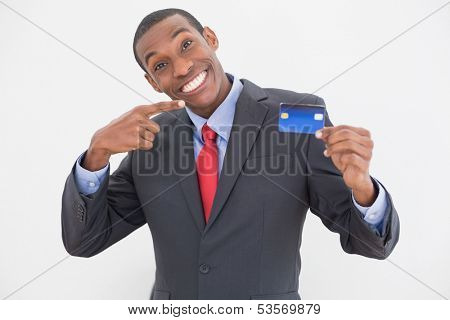 Portrait of a cheerful young Afro businessman pointing at credit card over white background
