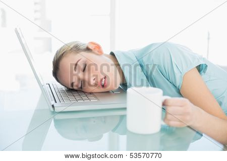 Young exhausted businesswoman sleeping sitting on her swivel chair lying with her head on her notebook