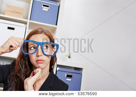 Pensive woman in office holding oversized nerd glasses