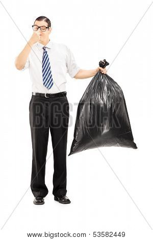 Full length portrait of a male closing his nose and holding a stinky garbage bag isolated on white background