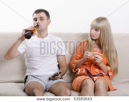 The pair on the couch. He looks drinking beer, she looks at him reproachfully
