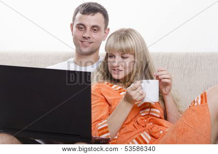 The guy sitting with his laptop on the couch, sitting next to a girl with a Cup of tea