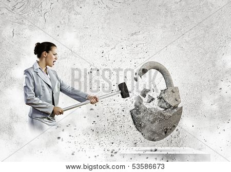 Image of businesswoman crashing lock with hammer