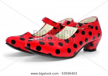 a pair of dot-patterned red flamenco shoes, typical of Spain, on a white background