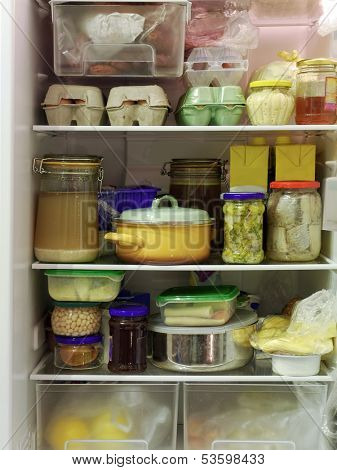 Refrigerator inside full of assorted food ingredients, fruit, vegetables, meat and dairy products