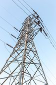 stock photo of utility pole  - High Voltage Electrical Towers In Line on blue sky - JPG