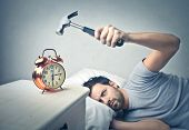 stock photo of ironic  - lazy man splits alarm clock with hammer - JPG