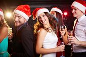 picture of flute  - Company of friends in Santa caps holding flutes of champagne while dancing at Christmas party - JPG