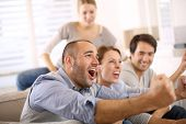 stock photo of indoor games  - Cheerful group of friends watching football game on tv - JPG
