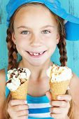 Portrait of 7 years old kid girl eating tasty ice cream over blue