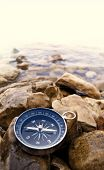pic of longitude  - compass on the bank with water and cobbles - JPG