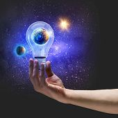 Image of human hand holding bulb with earth planet inside. Elements of this image are furnished by N