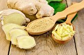 picture of condiment  - Grated and ground ginger in two wooden spoons ginger root green leaves on the wooden board - JPG