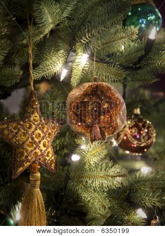 Golden Star And Pomegranate Decorations On Christmas Tree.