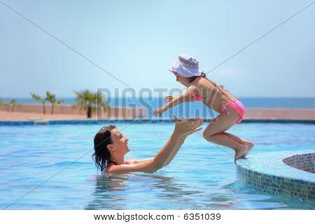 schöne Frau fängt kleines Mädchen im Pool gegen Meer springen