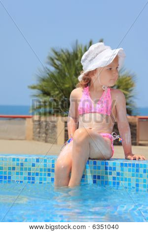Pretty Little Girl Smeared With Cream For Sunburn Wets Feet Water In Pool Against Sea
