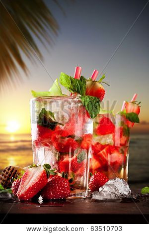 Mojito drinks on stone with evening blur ocean shore background