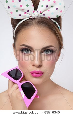 Portrait of young beautiful sexy tanned girl with fancy hairband and vintage sunglasses in her hand