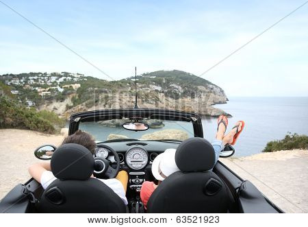 Couple sitting in convertible car and looking at panorama