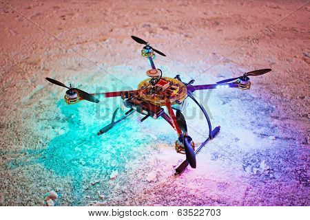 Unmanned quadrocopter landed on snow in winter evening