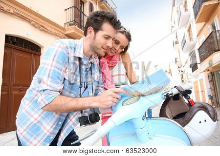 Tourists in Ibiza with scooter looking at city map