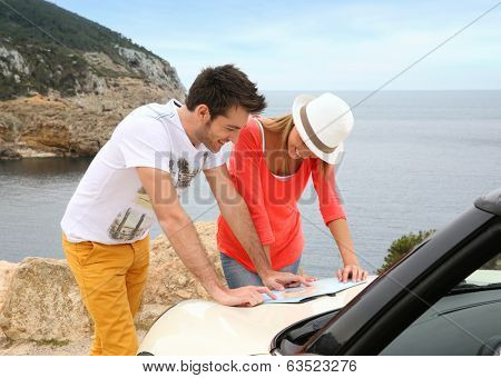 Couple reading map on road trip with cabriolet