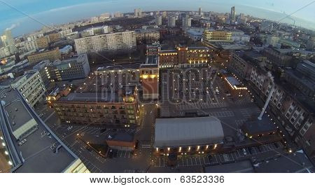 Cars on parking in courtyard among buildings at evening. Aerial view
