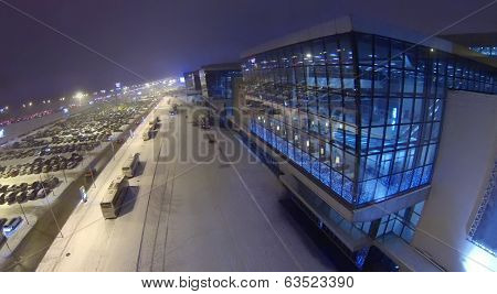 Many cars on big parking close to shopping center at dark winter night. Aerial view