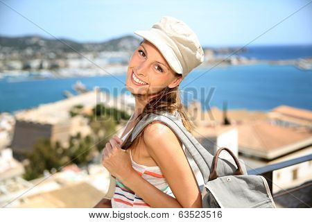 Smiling tourist girl with backpack visiting Balearic Island