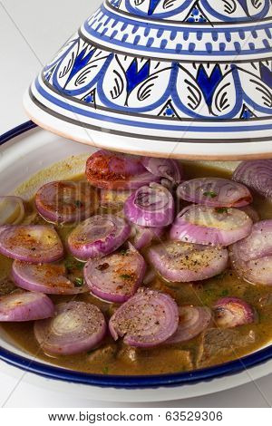 A Moroccan tagine with half-cooked beef, raw onion and spices, ready to go in the oven