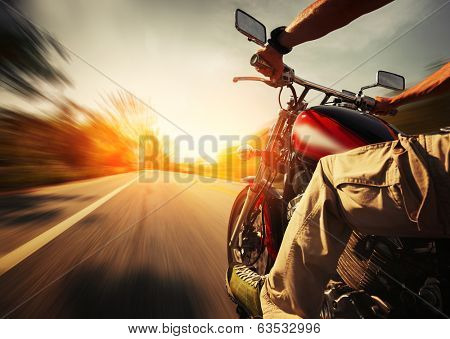 Biker riding motorcycle  on an empty road at sunny day