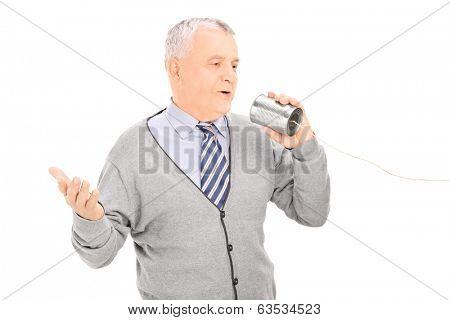 Senior man talking through a tin can phone isolated on white background