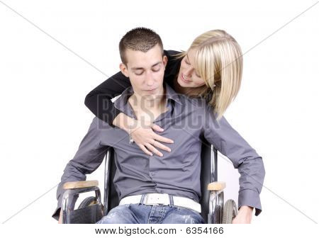 Young Woman Taking Care Of A Young Man In A Wheelchair