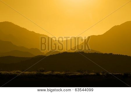 Silhouette Of Mountain Range Layered In Amber