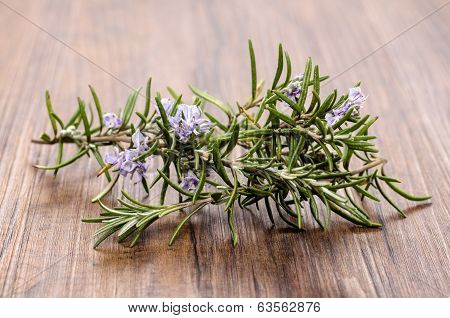 Rosemary With Flowers On Wood