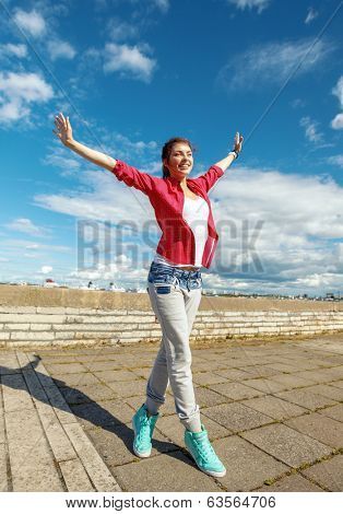 sport, dancing and urban culture concept - beautiful dancing girl in movement with raised hands