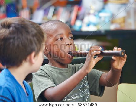African child playing flute in a music school