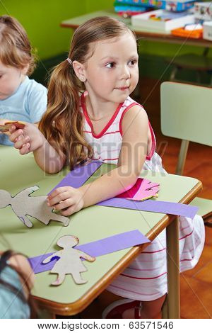 Children in a group  at the table doing arts & crafts in kindergarten