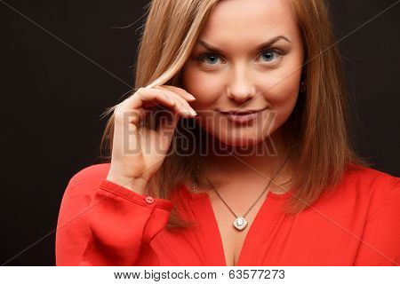 Beautiful business woman in red blouse over black background