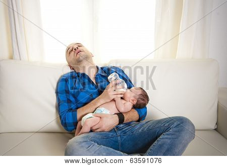 New Father Alseep While Feeding His Newborn Baby